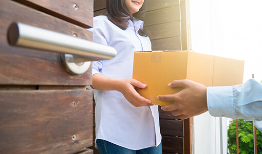 woman taking a box from delivery person